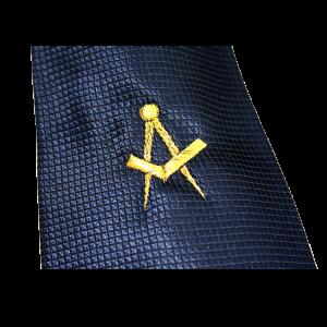 """dettaglio ricamo """"squadra e compasso"""" in oro su cravatta blu"""