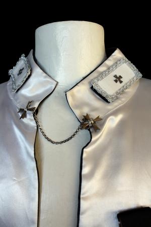 particolare del colletto mantello cavaliere templare, bianco con inserti in metallo